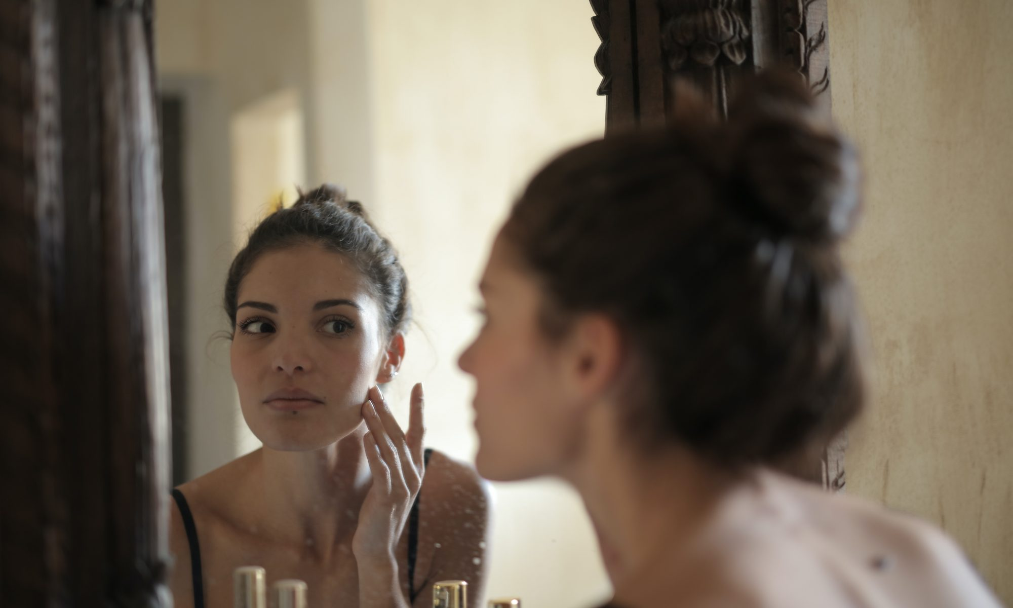 Woman checking her skin in the mirror